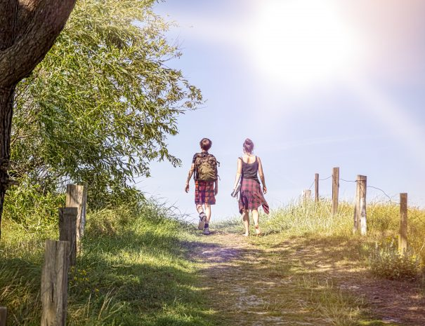 two teenager walking a path at noon